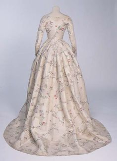 ca 1785-95. Open gown and petticoat of cream silk, painted with sprays of leaves, flowers and fruit, mainly in red, blue and green. The bodice is lined with white linen, is boned and comes to a sharp point at the back and features long, fitted sleeves. Gown skirt is cut with a wide circular train. Silk painted in China, exported to Britain, and made up by a mantua-maker.