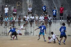 Youth compete in the Sao Carlos slum local soccer tournament in Rio de Janeiro, Brazil. The pitch is just dirt and the incandescent lights aren't so bright. But when the boys' feet strike the football in the Sao Carlos slum as night falls every Saturday, big league dreams glow, inflated by the hope of escaping the shantytown with sporting skills. Photo: AP Photo