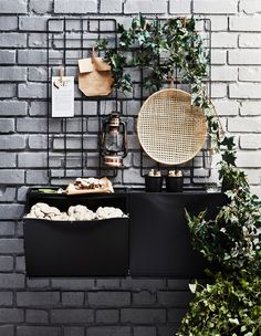 Sapateiras TRONES em preto penduradas numa parede de tijolos e usadas para cultivar cogumelos num espaço exterior