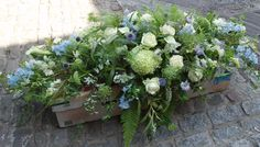 A large coffin spray in soft shades of blue, green and white with garden foliages.