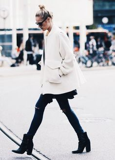 A white coat is worn with black ripped jeans, black boots and sunglasses.