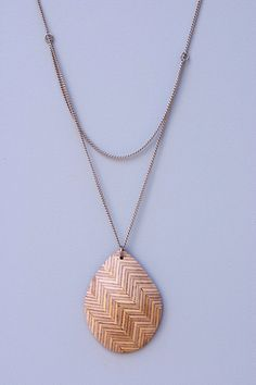 The Teardrop Chevron necklace is a cascade of repeating chevrons and silver chain that mesmerizes and inspires the eye .   These gems are salvaged in the making of furniture and feature versatile tones and texture. Variations in material and shape should be expected from what is shown in the images as every piece is made by hand.  $65