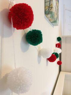 A lovingly handmade pom pom garland with 12 acrylic wool pom poms in a Christmas…