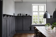 Swedish country house dining room, black lower wood panels and light gray upper. Distressed wood dining table, industrial style pendant light.... I love how this looks nice&comfortable instead of cold and stark, like it could with these colors. Black&Greg done RIGHT.