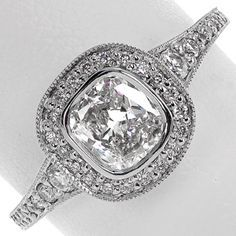 Beautiful diamond engagement ring with a simple, bezel set cushion cut center stone surrounded by a halo. The band flares out and the size of the side stones increase as it approaches the halo. Halo and band are both micro pave. Flare by Knox Jewelers