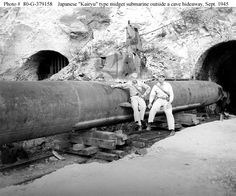 """Japanese """"Kairyu"""" Type Midget Submarine    Outside its cave hideaway in a Japanese coastal hillside, 22 September 1945. The men alongside it are from USS Boston (CA-68), one of whose photographers took this photo."""
