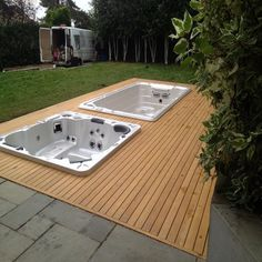 Sunken swim spa and hot tub surrounded by wooden Verda decking