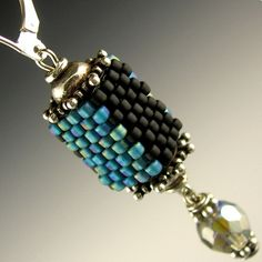 """These earrings are constructed from Japanese glass seed beads in frosted iridescent teal, aurora borealis smoke-colored Czech firepolished glass beads, sterling silver beadcaps, and sterling silver leverbacks. The rectangular cube segments are created with a needle and thread, one bead at a time, using a handweaving technique called """"peyote stitch"""". Measurements: Length: 1.75""""/4.5 cm Width: 0.4""""/1 cm"""