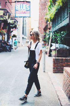 White tee and black overalls.