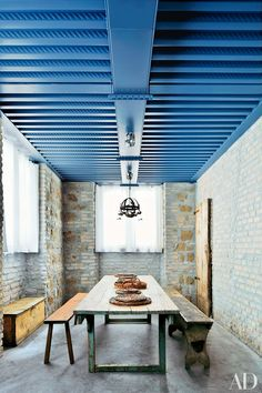 Farmhouse furniture stands beneath a beamed metal ceiling in in the Rome studio space of pianists Katia and Marielle Labèque, decorated by Axel Vervoordt.