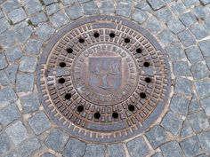 The manhole covers in Kühlungsborn show the city arms. The coat of arms displays three silver seagulls in a blue field. The title Ostseebad refers to the fact, that Kühlungsborn is a seaside resort on the Baltic Sea (Ostsee). Seaside Resort, Pan Set, Baltic Sea, Coat Of Arms, Peter Pan, Metal Working, Germany, Urban, Cover