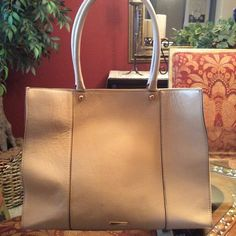 Listing Rebecca Minkoff Med MAB Tote in Biscuit Soft saffiano leather, dual top handles, rose gold hardware, magnetic top & original dust cover. This classic structured bag is edgy yet feminine. Large enough for a laptop. Ideal for an everyday bag & perfect for travel. Gently used & in very good condition. However, a black Sharpie pen leaked in the interior pouch. See photo. Fortunately, the fabric is a black & white pattern so it's not a glaring spot. Shows some wear & few small marks on…