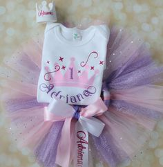 Personalized princess first birthday party smash cake outfit done in lavender purple, baby light pink, hot pink, and a touch of white outfit set. Personalized crown, shirt, and tutu all coordinated with sparkling glitter is perfect for those first birthday photos!