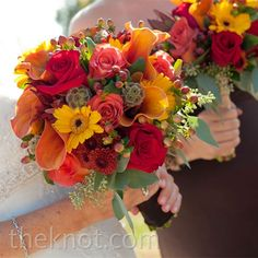 seasonal bouquet includes spider mums, sunflowers, hypericum berries, eucalyptus, and Leonidas roses, along with a fresh hint of greenery