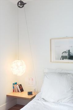 """For a simple, low-cost bedside reading light with a dash of industrial style, Bernier ran a standard-issue cord set through a vintage clothesline pulley, which he picked up at a flea market, on Thibault's side of the bed. 'If she ever wants it to be higher, she can easily adjust it,' he says."""