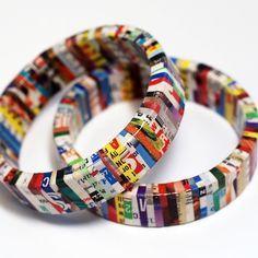 Divertidas pulseras reciclada hechas de retazos de viejas revistas cuidadosamente envueltos alrededor de una base de madera o plástico. Se las ha revestido con un sellador brillante o barniz para que sean resistentes al agua o la humedad.