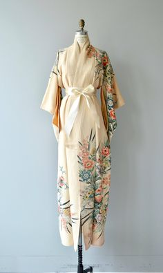Vintage 1950s cream silk kimono with pastel wildflower reaching across the shoulders, down a sleeve and the length of the kimono. Short furisode sleeves and wide cream ribbon sash. ✂-----Measurements fits like: fits most bust: free waist: free length: 59 brand/maker: n/a condition: excellent ✩ layaway is available for this item to ensure a good fit, please read the sizing guide: http://www.etsy.com/shop/DearGolden/policy ✩ visit the shop ✩ http:/&#x...