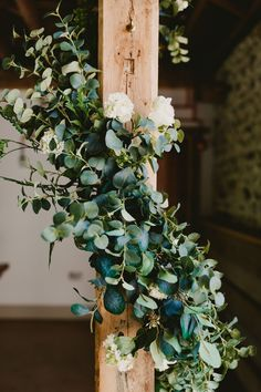 Faux greenery wrapped around a beam for a barn wedding. Hire these fake garlands from Friend of Faux.