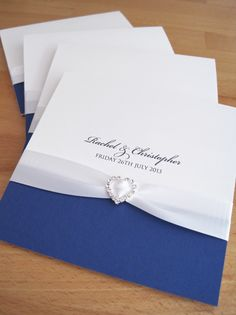 Albany Pocketfold Wedding Invitations in white and royal blue and finished with white ribbon and a crystal heart.