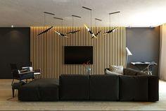 lambris mural en lamelles, suspensions et canapé noir dans le salon
