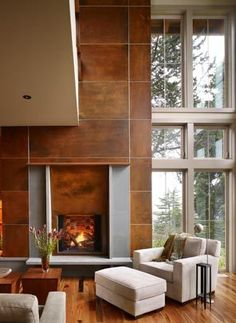 The huge volume of space is warmed up with wooden floors, deep, cozy chairs and a fireplace clad in rusted steel panels that look soft as suede. The two-story-high bank of windows looks west to Puget Sound.