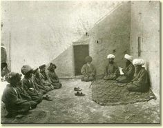 A judge (with a white turban seated in the center of the 'ertman gol' Chodor rug) reads from a paper, apparently rendering judgement in some dispute.