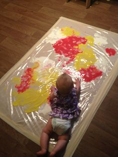 NO MESS PAINTING for my infant and toddler classroom. Mixing colors and making footprints. The infants even joined the action by having tummy time and exploring the colors. Very easy and cheap idea!!!