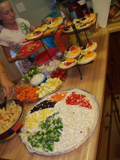 Beach Ball Party snack table - beach ball veggie pizza, veggie tray, fruit pizza beach ball cookies, and other bright colored snacks