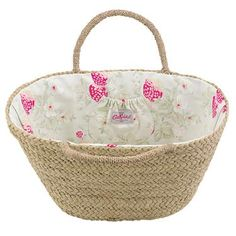 Perfect for summer or a day at the beach, this spacious straw basket has sturdy grab handles and a pretty Wild Strawberry lining.