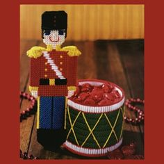 "Nutcracker Candy Dish Plastic Canvas ePattern - This handsome soldier will happily stand guard over your Christmas goodies! The toy ""drum"" is actually a candy dish that'll keep treats in sight for your holiday guests. The design is stitched using worsted weight yarn, 7 mesh plastic canvas, and a 4-1/2"" plastic canvas circle. Number of Designs: 1 candy dishApproximate Design Size: 7""w x 10""h x 4-1/2""d"