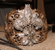 Fleur de lis cuff. The Fleur de lis (Flower of the Lily) represents the Trinity. This beautiful design has Jesus in the middle of the design.
