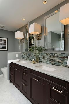 This gray contemporary bathroom features a double-vanity design with a Carrera marble countertop, glass-tile backsplash, and polished chrome sconces and fixtures. The sleek mirrored medicine cabinets add storage and polish to the space. by earnestine Dark Wood Bathroom, White Bathroom, Bathroom Marble, Glass Tile Backsplash, Vanity Backsplash, Backsplash Ideas Bathroom, Backsplash Cheap, Quartz Backsplash, Backsplash Panels