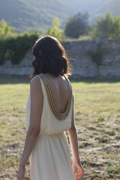 Pretty. Very Greek like, open back, cream color with a little gold.  Yes, pretty