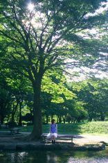 Young woman sitting on a bench at a park. stock photo