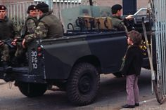 BELFAST, UNITED KINGDOM-MAY 1972. British Army soldiers driving past a boy holding flowers in West Belfast during The Troubles, Northern Ireland. (Photo by Alain Le Garsmeur/Getty Images)