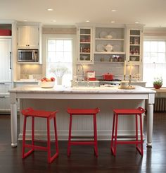 White Kitchen with pops of red. White kitchen with red decor. White Kitchen with red counterstools and decor. The subway tile backsplash is Waterworks ... & Get the Look: Bright White Spaces | Bright Kitchens and Spaces islam-shia.org