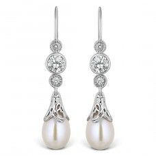 Ula Diamond, Pearl & CZ Earrings Our 'Ula' earrings, which means jewel of the sea, have been designed to maximise the beauty of the natural pearl. Each pearl is held in place by beautifuil delicate scroll work which in turn hangs from quality Cubic Zirconia stones. This is all finished off with real diamonds giving these earrings a classically sophisticated look. Lavishly coated with rhodium plating. Total drop length 34mm*.  *all measurements are approximate.
