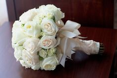 white roses with a beautiful bow finish  www.buffaloweddingflorist.com