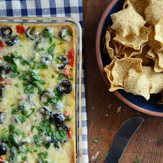 Cheesy Warm Bean Dip Recipe Appetizers with refried pinto beans, cream cheese, low-fat plain yogurt, onion, cumin, chili powder, dried oregano, garlic powder, salt, black pepper, sharp white cheddar cheese, cherry tomatoes, pitted black olives, parsley leaves, tortilla chips