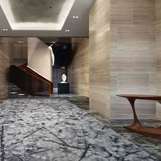 Stylish, spirited and considered, the interiors of this hotel capture the verve of New York City.  The entry is wrapped in honed silvery-veined stone, cool grey stone floors and custom watercolor-inspired rugs.  #parkhyattnewyork #YPprojects