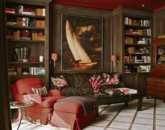 25 Inspiring Home Libraries - red chair. dark. interior. books. sailboat. sconce.
