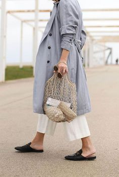 A Month's Worth Of Chic Spring Outfits: Fashion blogger 'My Daily Style' wearing a pale blue trench coat, white straight crop trousers, black loafer mules and a beige net bag. Spring outfits, casual outfits, fashion trends 2018, casual outfits, comfy outfits #fashion2018 #casualstyle #springstyle #streetstyle #ootd #fashionblogger #trenchcoat #mules