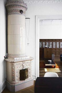 Swedish ceramic fireplace. En stilig kolonnkakelugn står i ett hörn av matrummet, pyntad med en ljusstake från Ikea och ängel...