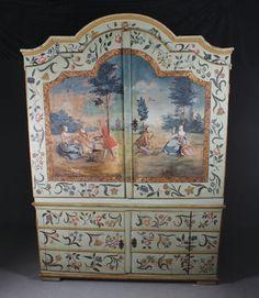 Rikt dekorert skap av Peder Aadnes (1739-1792) eller hans krets. Overskap med to dører, rikt dekorert med landskapsmotiver med mennesker og blomsterranker rundt. Underdel med to dører malt med blomsterranker. Sidene dekorert med trær. Bærehåndtak på sidene, innv. med hyller. H: 235 cm. B: 170 cm. D: 56 cm. Noen mindre rep., noe slitasje/avflassinger og sprekk på dør nede. Prisantydning: ( 450000 - )