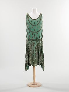 Fantasy flapper      c. 1925  The Met says: …Ladies wearing these slightly revealing dresses, made of delicate fabrics and decorated with heavy beading were often referred to as flappers. This dress is a wonderful example of the style of the period. An unusual pattern of free-form elements concentrically outlined in clear beads enlivens this piece and the textured surface of the sequins creates an interesting play of light.