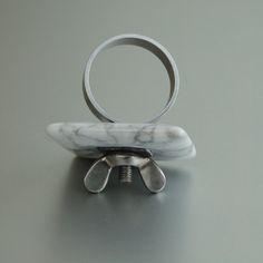 Prsten Čtverec bílý Výrazný prsten z kolekce Křídlovky. Použit je magnezit / howlit od nulkyjanulky-minerály. Střed tvoří za tepla zalisovaný šedavý plast. Horní část, ve kterém je závit, je našroubována na prsten a dotažena křídlovou matkou, takže se neuvolňuje. Můžete si koupit jeden prsten a postupně přikupovat další díly z různých materiálů a jako ...