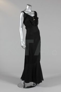 A black chiffon evening gown, circa 1935, with pleated bands of chiffon and rosette flounce held in two rhinestone circlets on the breast, bands carry round to the back and are held in place by a large vertical triple-looped medallion similar, two long floating panels radiate from the lower waist