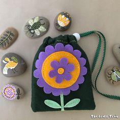 A fun rock painting craft inspired by traditional folk art. Store the rocks in a matching hand-sewn felt bag – with free printable pdf pattern