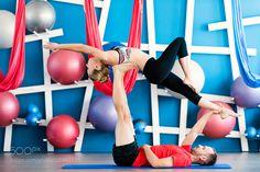 Couple practicing acro yoga in a studio. Acro yoga concept. Couple yoga class workout