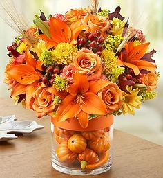 Orange - roses, lilies, carnations, leaves and berries.